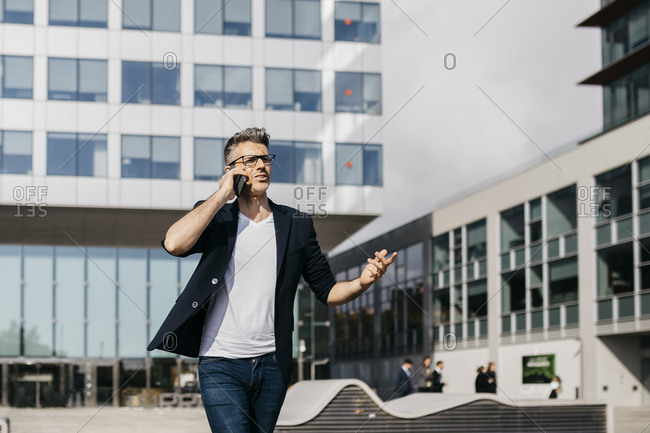 Angry businessman on cell phone walking outside office building