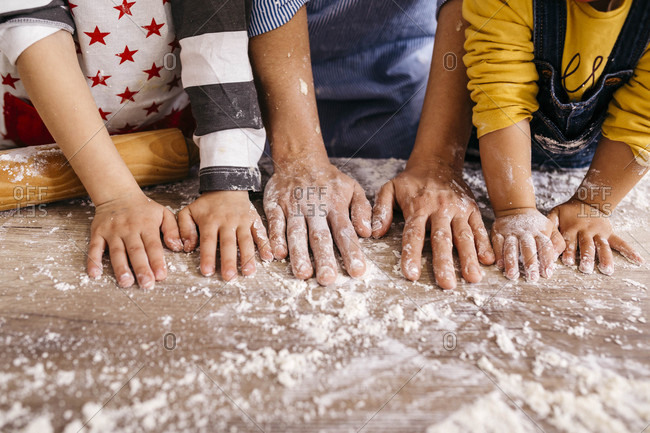 Mother and children with flour on their hands- partial view