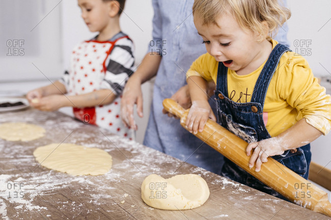 Excited toddler girl rolling out dough with wooden rolling pin