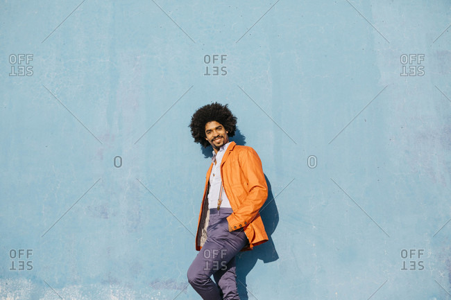 Portrait of stylish man leaning against blue wall