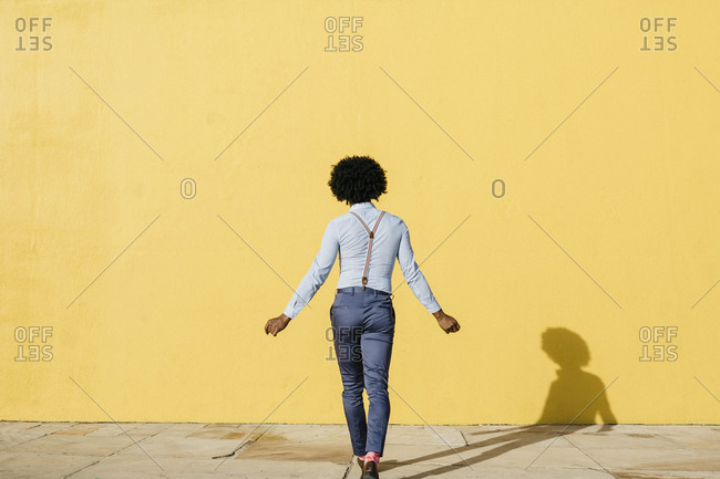 Back view of man wearing suspenders dancing in front of yellow wall