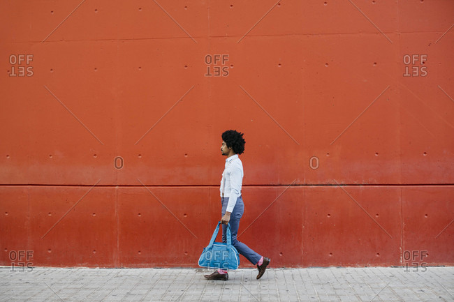 Man with bag walking down the street in front of a red wall