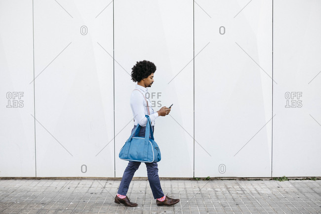 Man with bag walking in front of a white wall while looking at cell phone