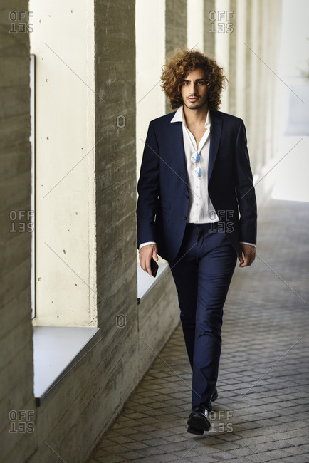 Portrait of young fashionable businessman with curly hair wearing blue suit