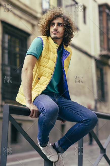 Portrait of young man with curly hair wearing yellow waistcoat sitting on railing