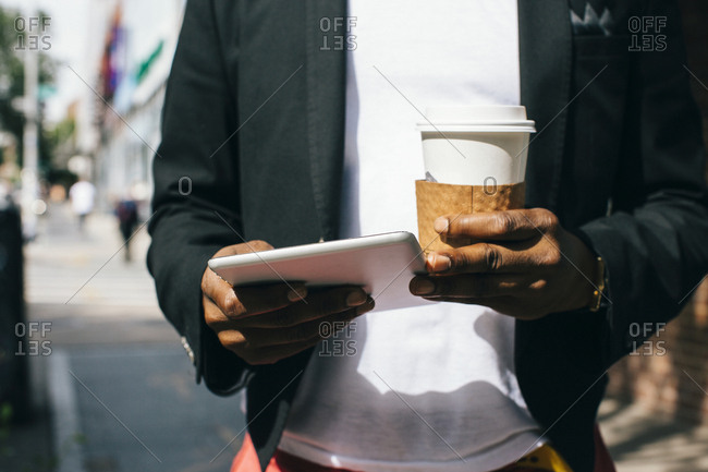 USA- NYC- Brooklyn- Man walking in the street- holding cup of coffee and digital tablet