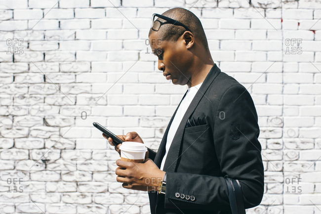 Mid adult man in front of white brick wall- holding smartphone and cup of coffee
