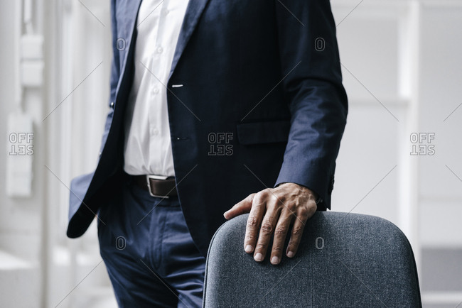 Businessman standing behind office chair- partial view