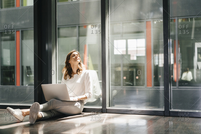 Businesswoman sitting on ground in empty office- using laptop