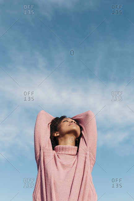 Relaxed young woman wearing pink turtleneck pullover enjoying fresh air