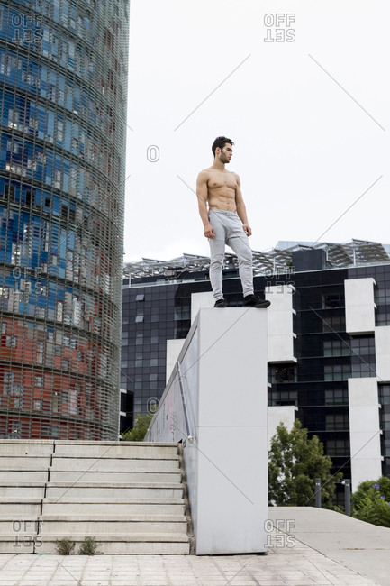 Young man during workout- standing on wall