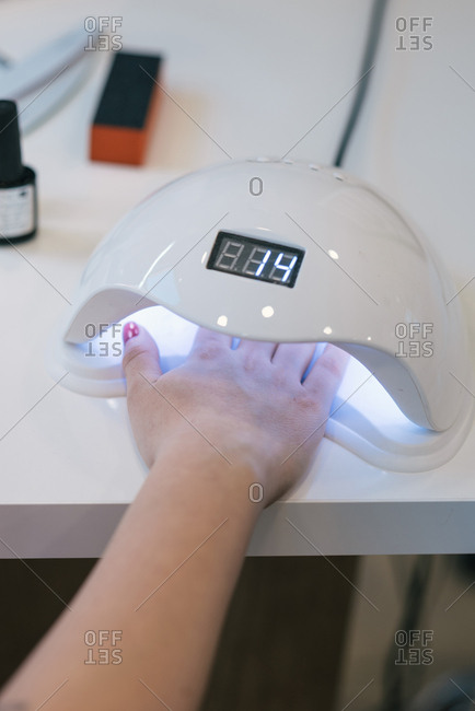 Woman's hand in UV lamp curing nail gel