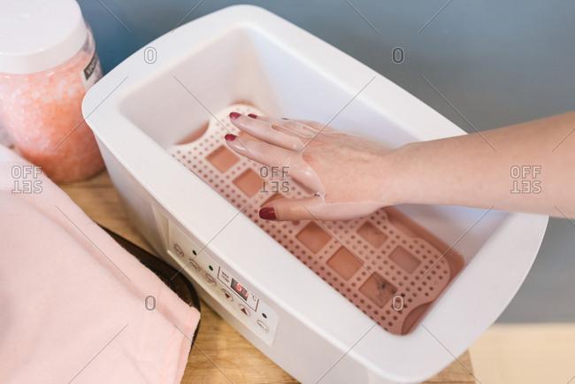 Woman's hand in paraffin wax bath