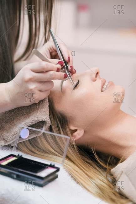 Cosmetician doing lash extensions on client