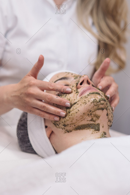 Cosmetician applying face peeling mask on a client
