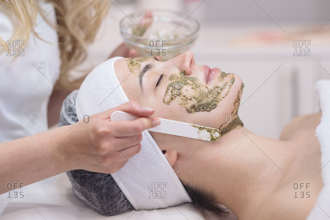 Cosmetician putting face peeling mask on a client