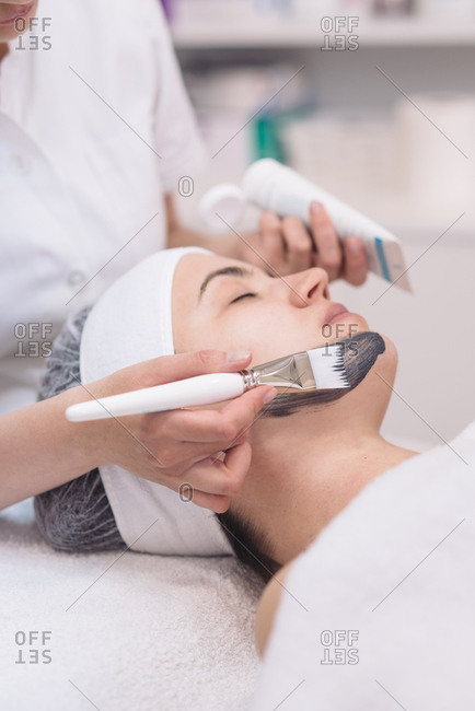 Cosmetician putting black face mask to the client