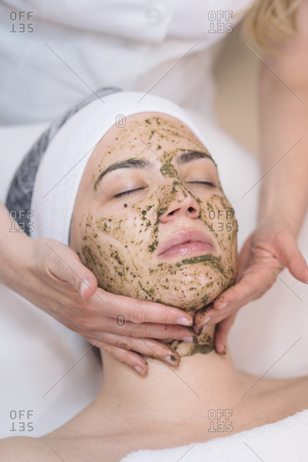 Cosmetologist putting face peeling mask on client