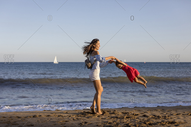 Mother and daughter having fun on the beach- pretending to fly
