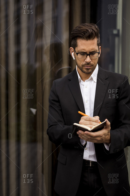 Businessman with earbuds in the city writing into diary