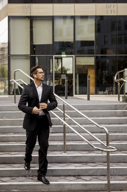 Businessman with earbuds walking on stairs in the city
