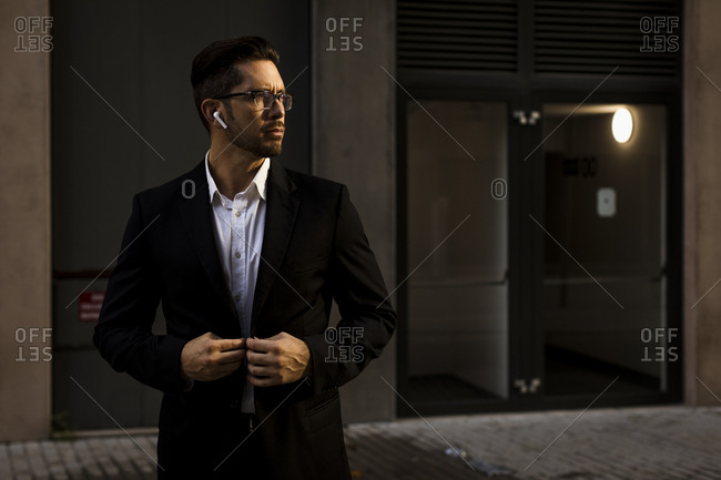 Businessman with earbuds in the city looking around