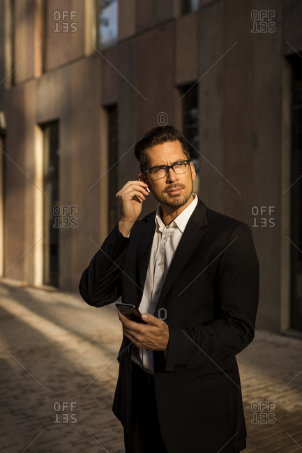 Businessman with cell phone and earbuds in the city looking around