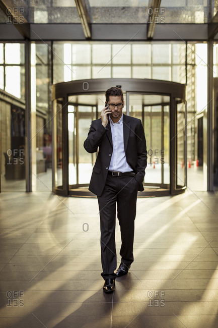 Businessman on cell phone in foyer of an office building