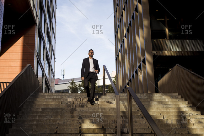Businessman walking down stairs in the city