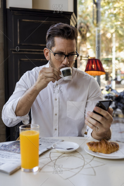 Businessman having breakfast in a cafe and checking cell phone