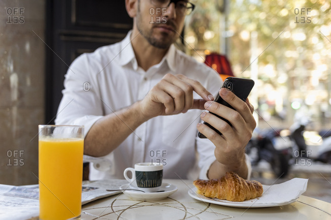 Businessman having breakfast in a cafe and using cell phone