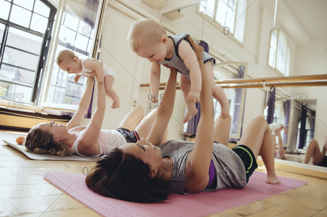 Two mothers working out on yoga mats while holding up their babies