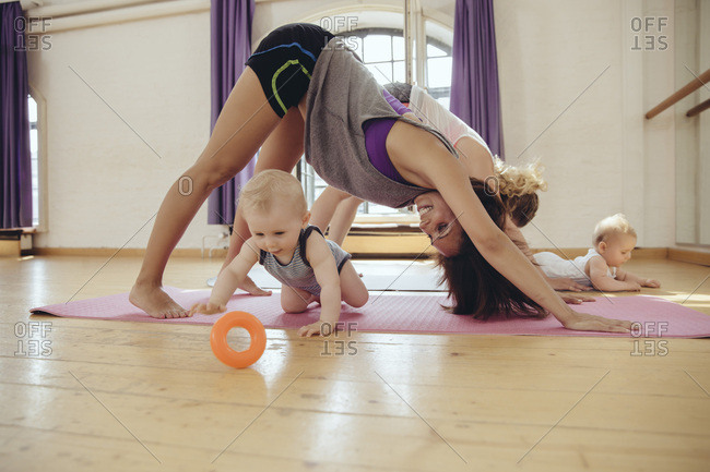 Two mothers working out on yoga mats with babies playing around them