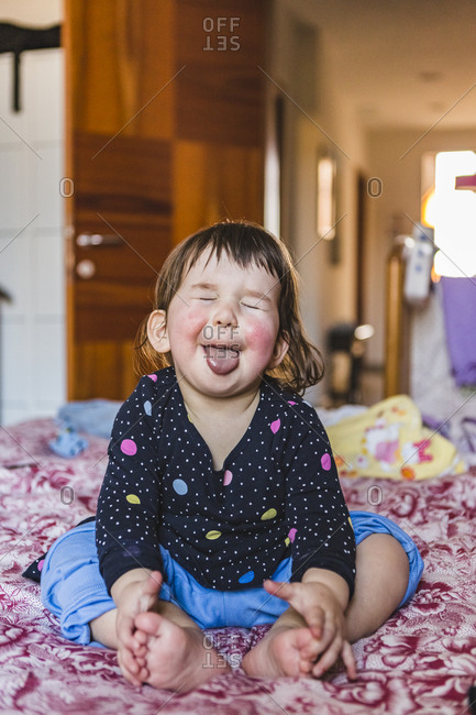 Portrait of toddler sitting barefoot on bed sticking out tongue