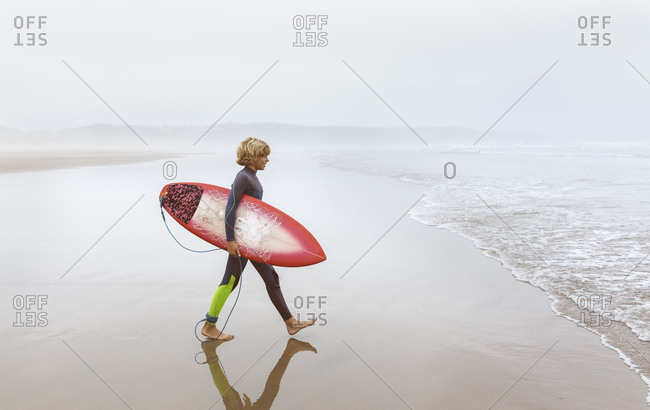Spain- Aviles- young surfer walking towards the water