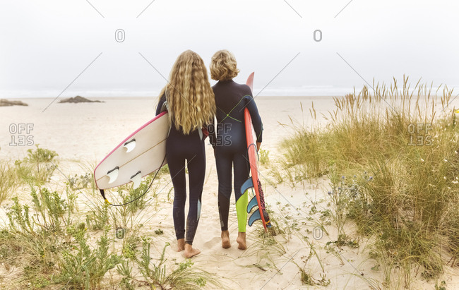 Spain- Aviles- rear view of two young surfers on the beach