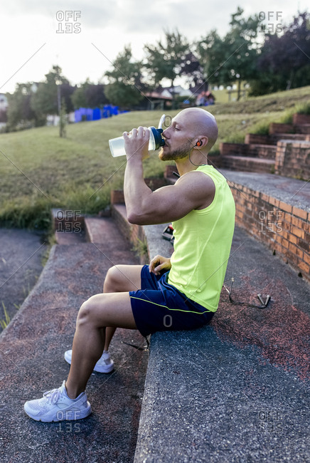 Muscular man having a break from exercising drinking water