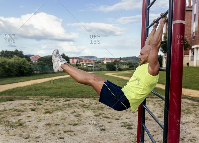 Muscular man exercising at a climbing frame outdoors
