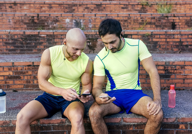 Two athletes sharing smartphones after workout