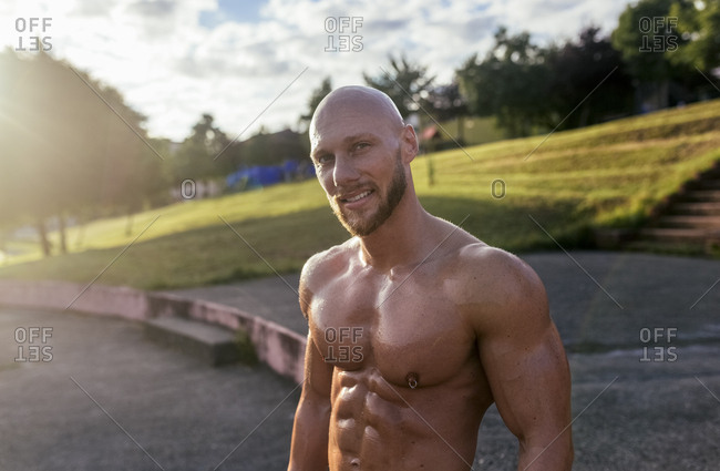 Portrait of smiling barechested muscular man outdoors