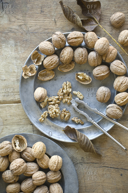 Whole and cracked organic walnuts and nutcracker on tin plates