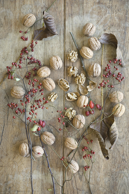 Whole and cracked organic walnuts- leaves and rosehips on wood