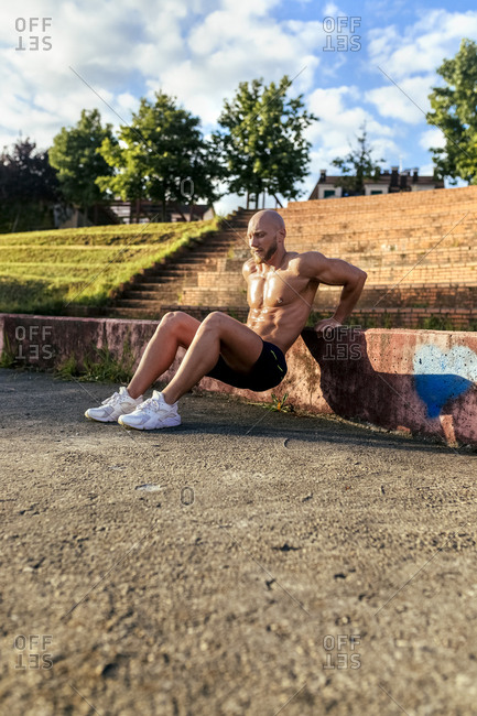Barechested muscular man exercising outdoors