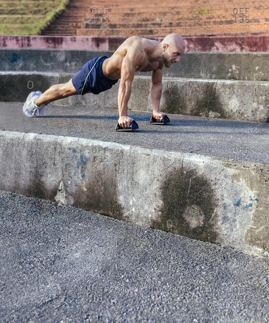 Barechested muscular man doing push-ups outdoors