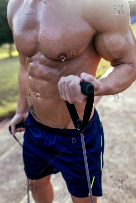 Mid-section of barechested muscular man exercising with expander outdoors