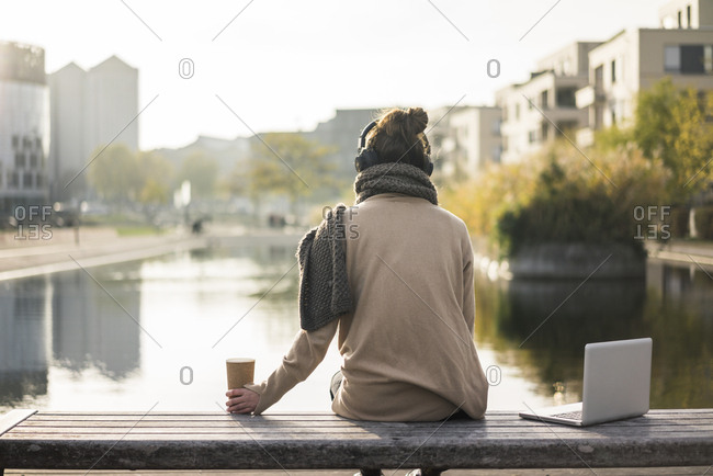 Back view of woman sitting on bench  with laptop and coffee to go listening music with headphones
