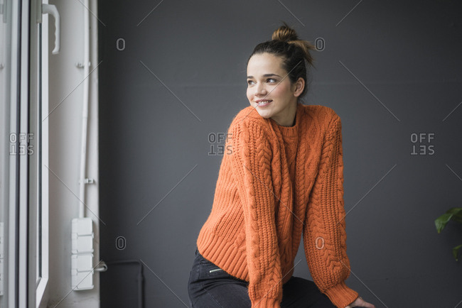 Portrait of smiling woman wearing orange knit pullover looking out of window
