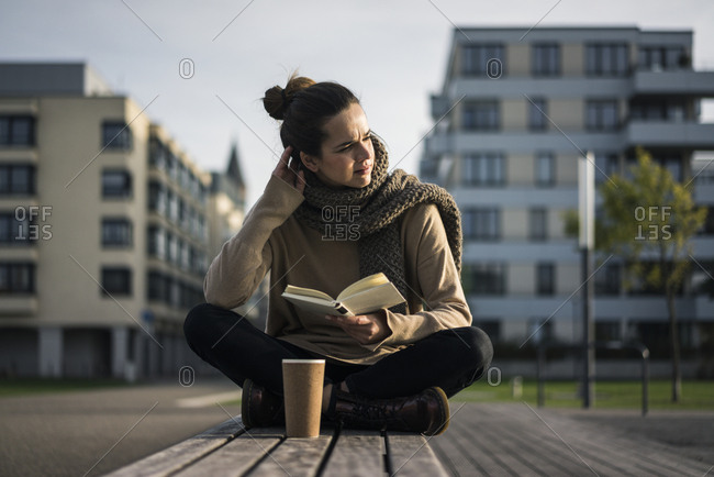Melancholy woman with coffee to go and book sitting on bench in autumn