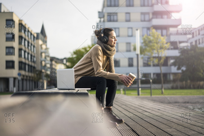 Woman with coffee to go sitting on bench in autumn listening music with laptop and cordless headphones
