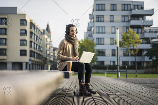 Woman sitting on bench with laptop and coffee to go listening music with cordless headphones